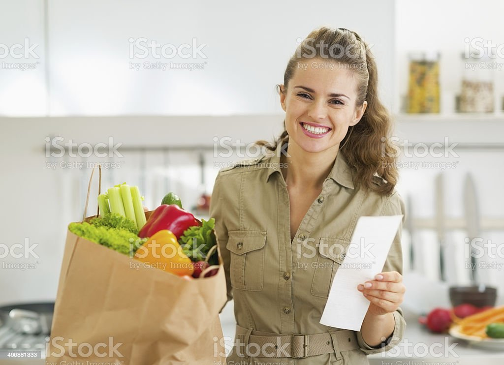 Smiling housewife with check and shopping bag full of vegetables stock photo