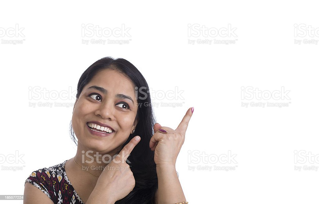 Smiling Indian Woman pointing at copy space for product royalty-free stock photo