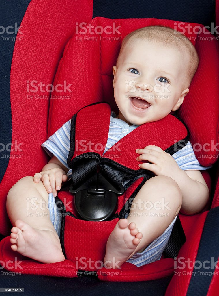 Smiling infant boy strapped in red car seat stock photo