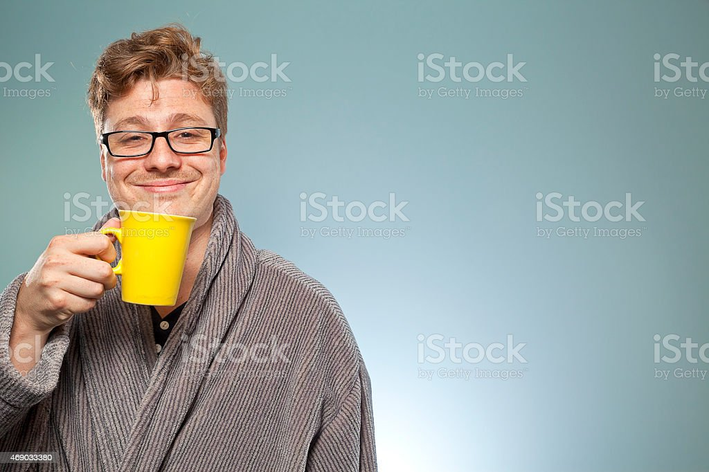 Smiling intelligent looking mature man drinks coffee stock photo