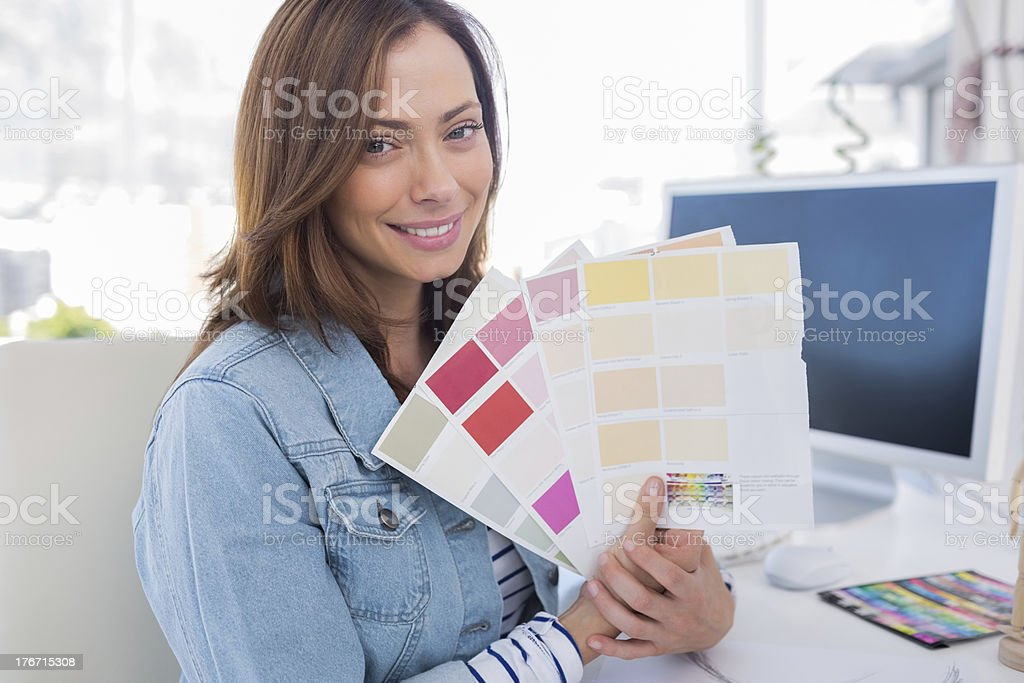 Smiling interior designer holding up colour samples royalty-free stock photo