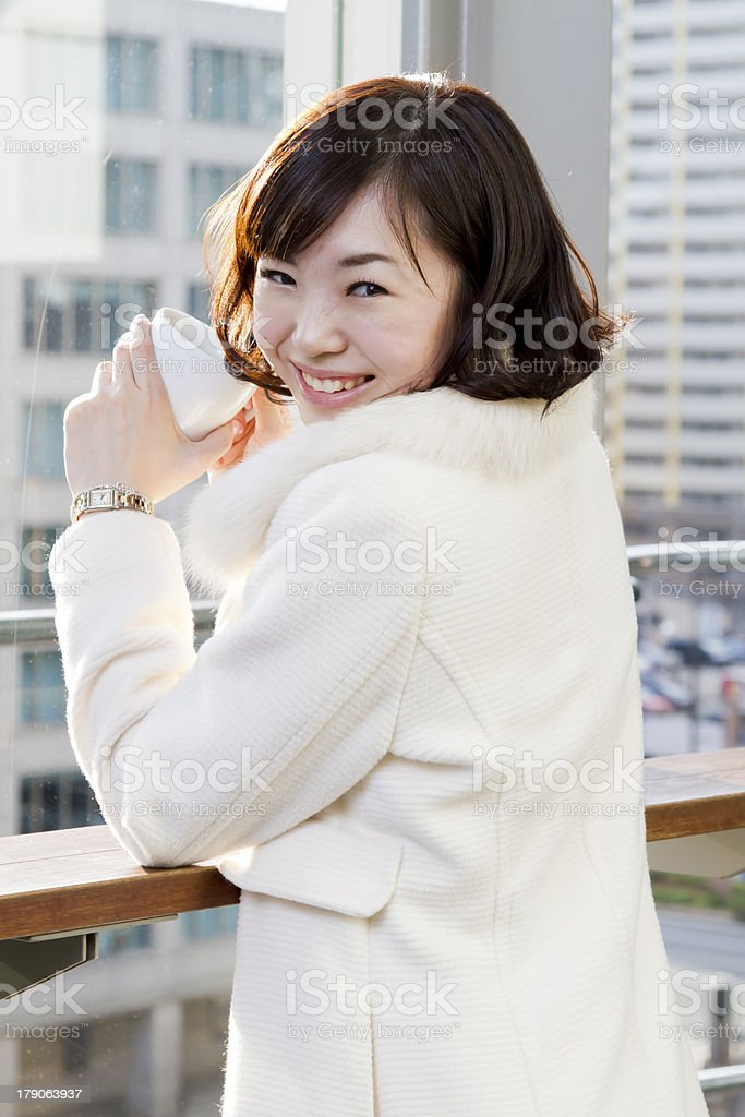 Smiling Japanese Girl Drinking Coffee in Front of Large Window royalty-free stock photo