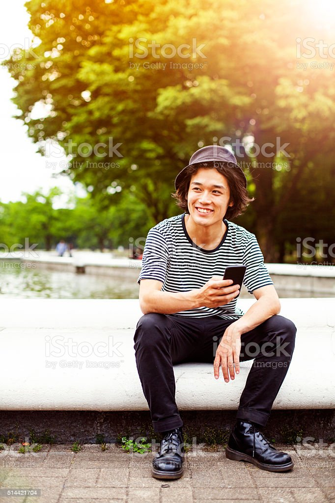 Smiling japanese teenager with smart phone in park, Tokyo. stock photo