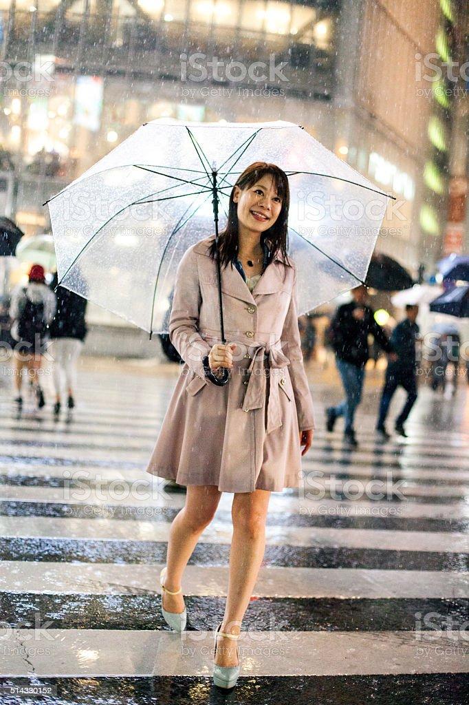 Smiling Japanese woman with umbrella crossing street in Shibuya, Tokyo stock photo