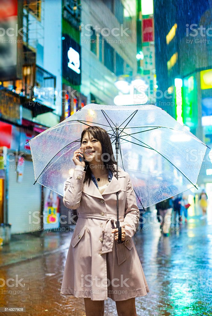 Smiling japanese woman with umbrella on the phone in Tokyo stock photo