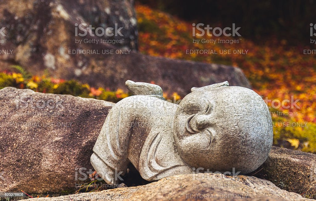 Smiling 'jizo' statue against autumn leaves stock photo