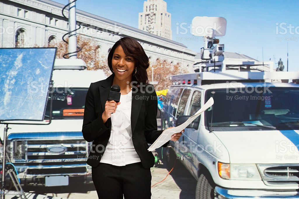 Smiling journalist standing outdoors stock photo