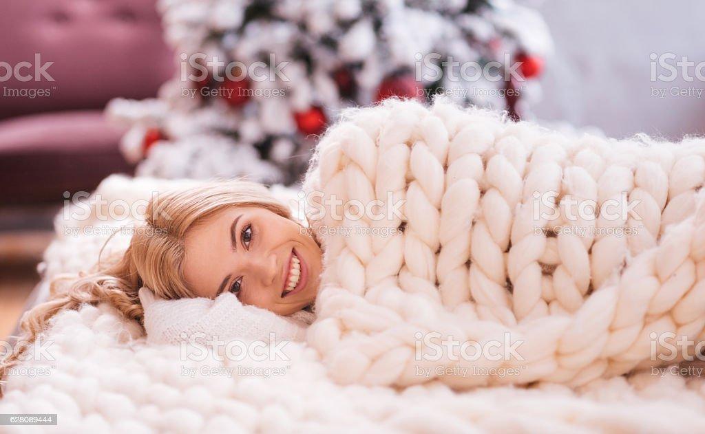 Smiling joyful woman lying under a warm blanket stock photo
