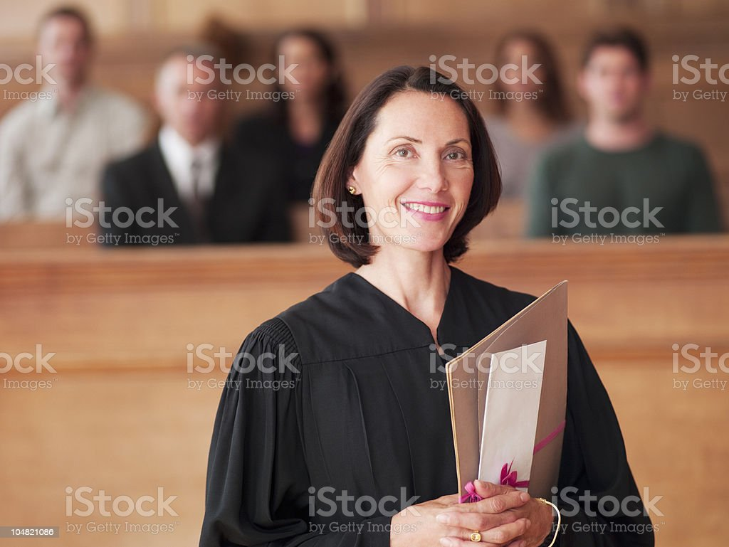 Smiling judge holding file in courtroom royalty-free stock photo