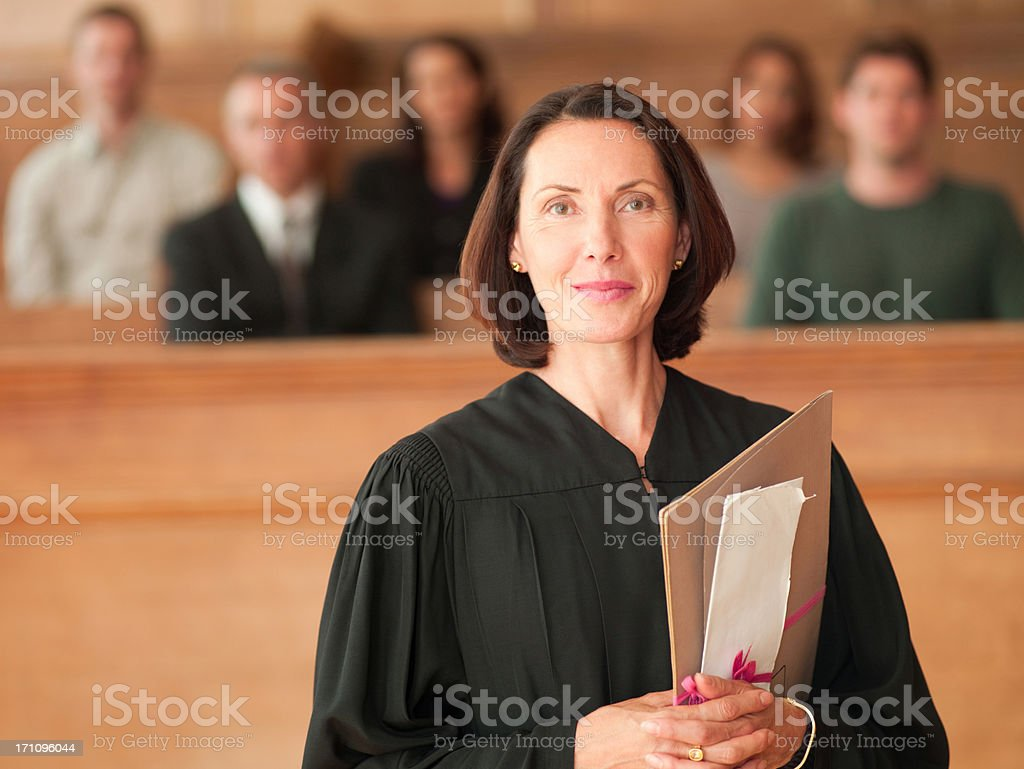 Smiling judge holding file in courtroom stock photo