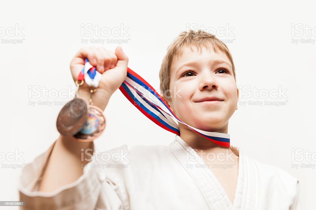 Smiling karate champion child boy gesturing for victory triumph stock photo