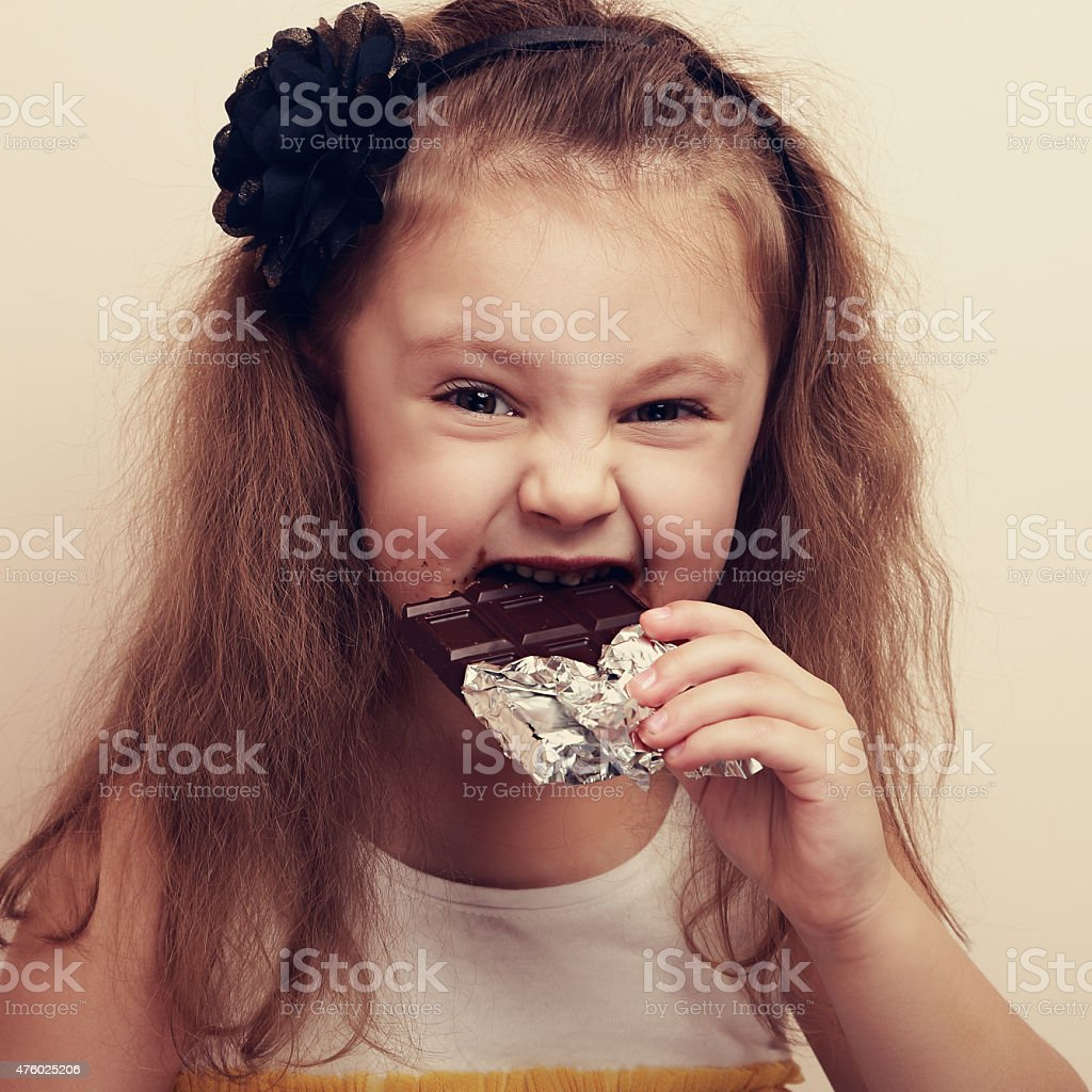 Smiling kid girl biting dark chocolate with craving fun eyes stock photo