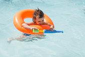 Smiling kid having fun in the pool with water gun.