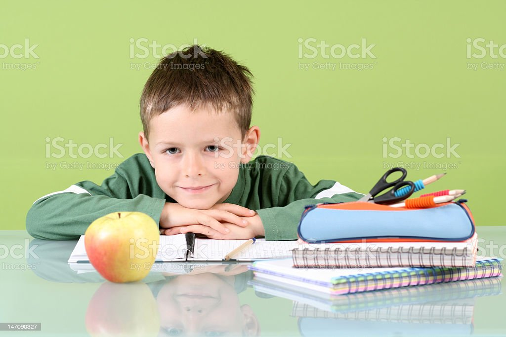 Smiling kid leaning on the table with an apple and homework royalty-free stock photo