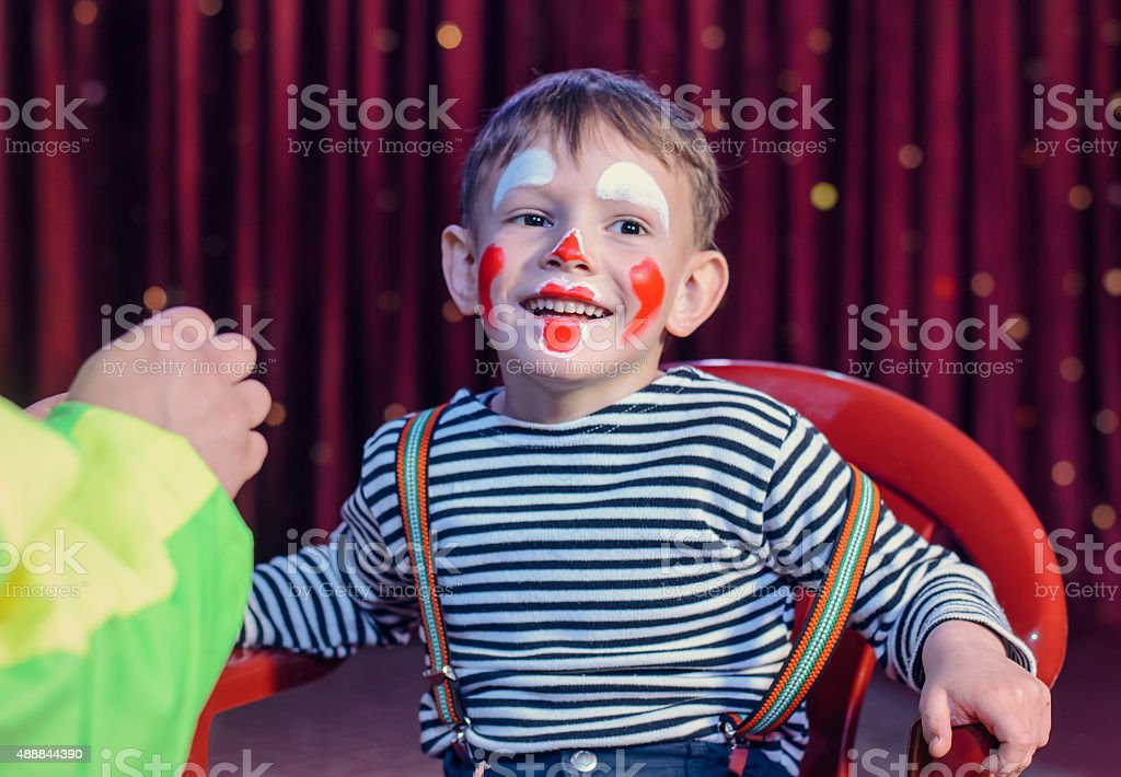 Smiling Kid with Funny Make up Sitting on a Chair stock photo