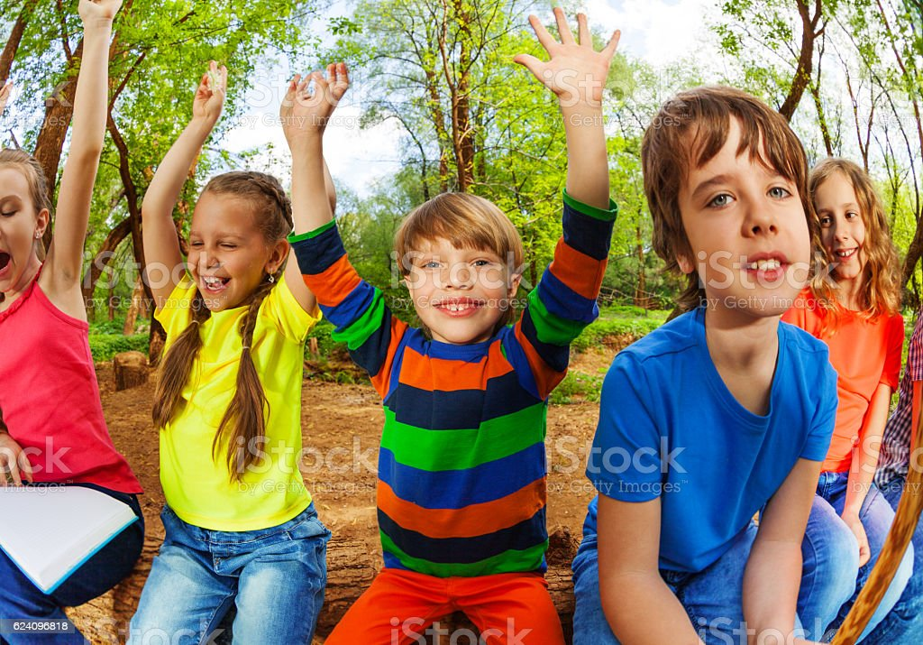 Smiling kids in summer forest with their hands up stock photo