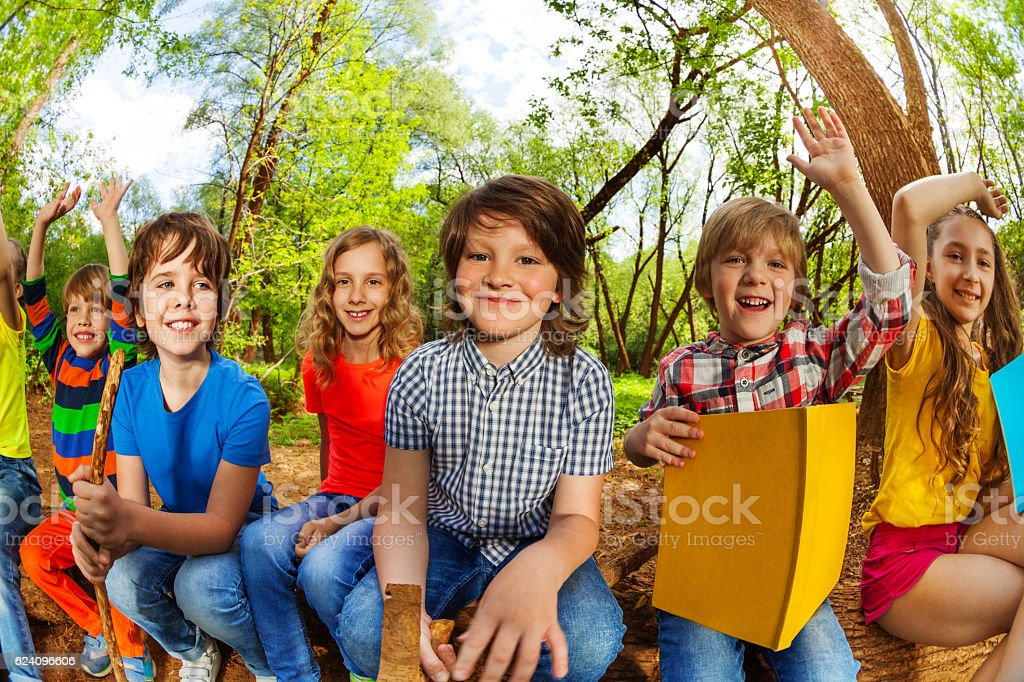 Smiling kids reading a book in the summer forest stock photo