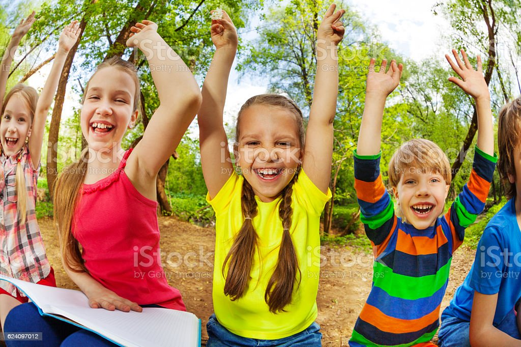 Smiling kids reading a book sitting in the forest stock photo