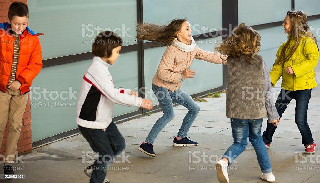 Smiling kids running around while playing at tag stock photo