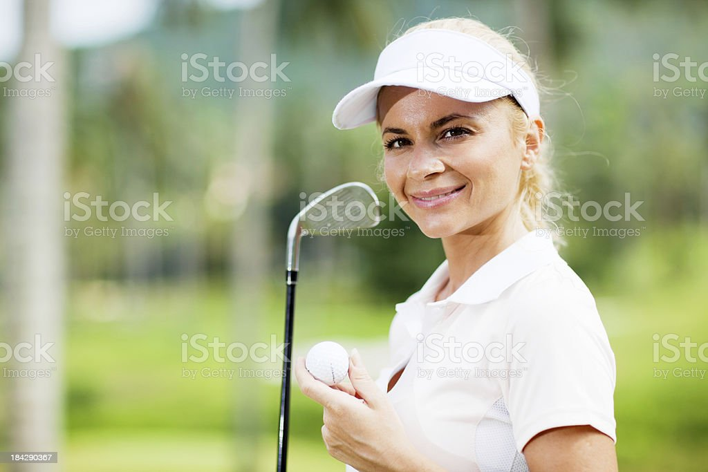 Smiling lady golfer with golf ball and stick. royalty-free stock photo