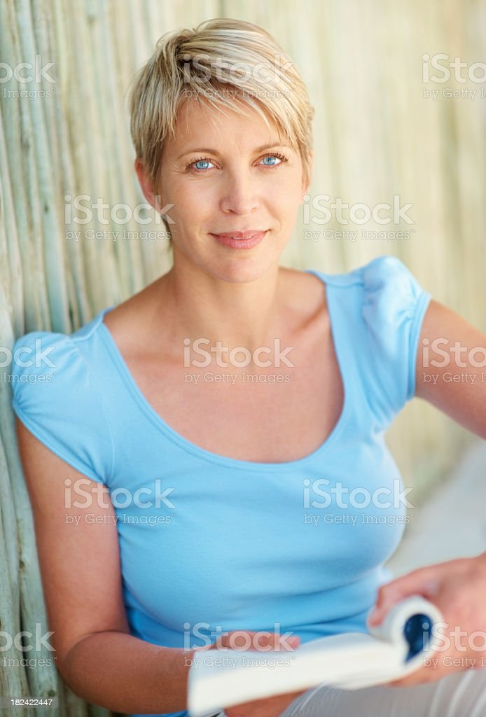 Smiling lady reading a book against bamboo wall royalty-free stock photo