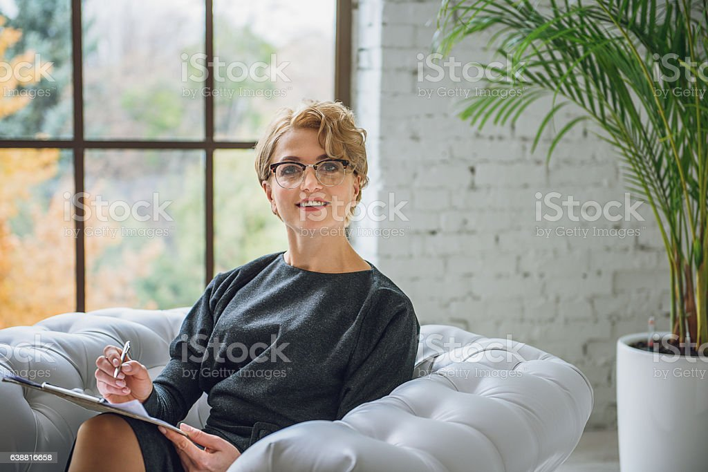 Smiling lady siting on couch stock photo