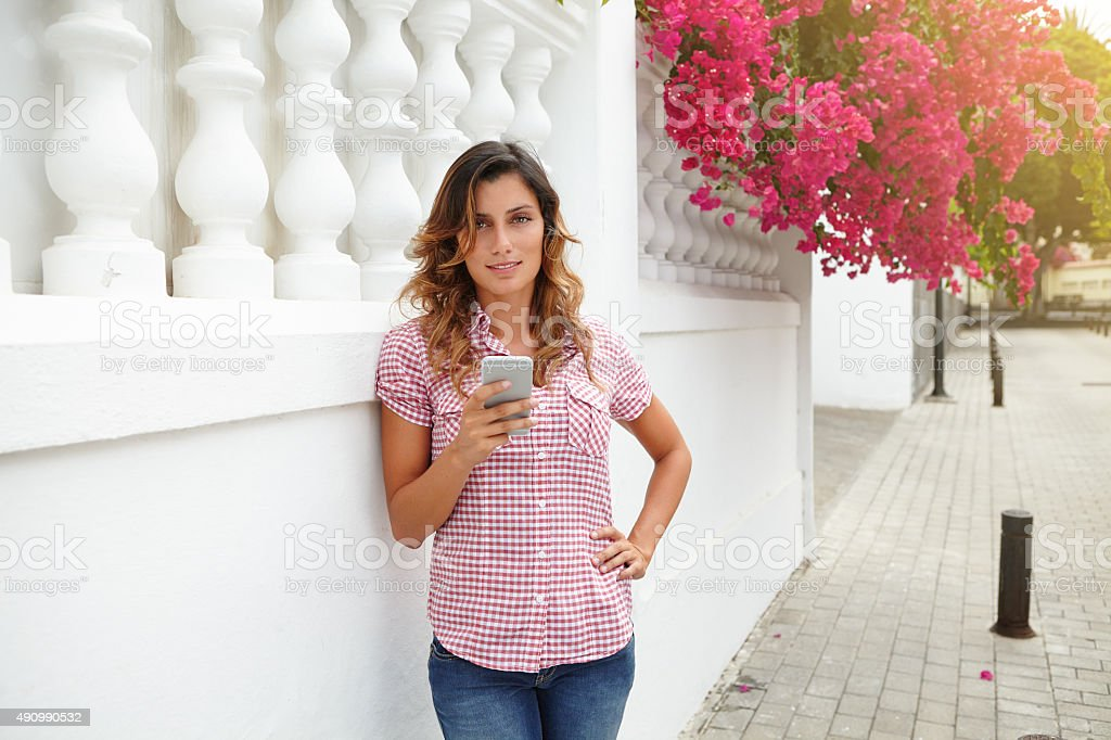 Smiling lady using mobile phone outdoors stock photo