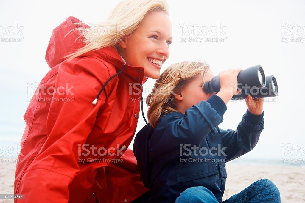 Smiling lady with little daughter looking through binoculars royalty-free stock photo