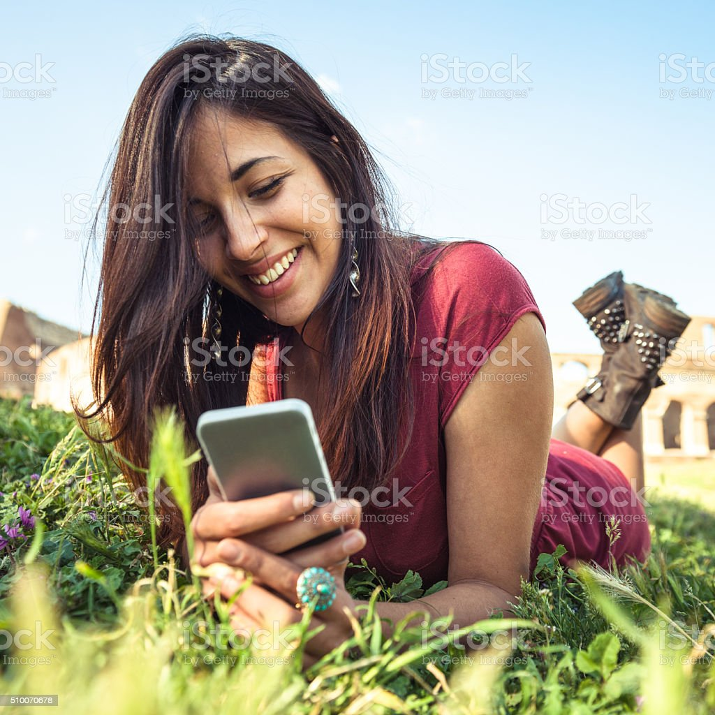 smiling latin woman lying down using the smartphone stock photo