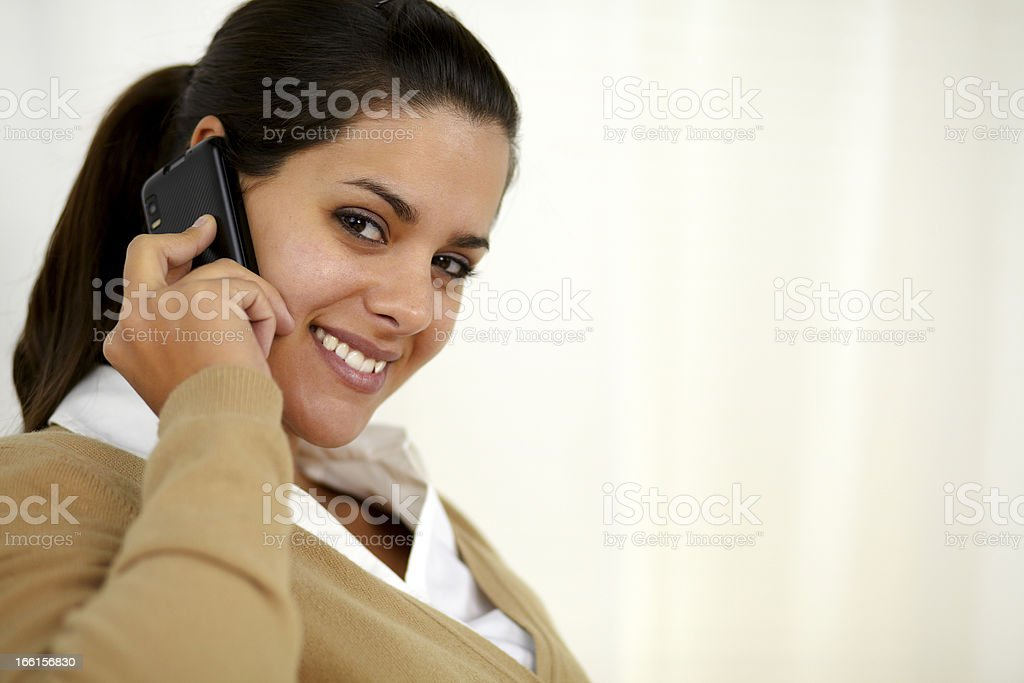 Smiling latin young female speaking on cellphone royalty-free stock photo