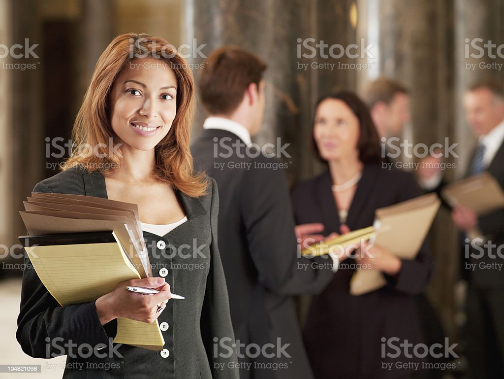 Smiling lawyer holding files in corridor stock photo