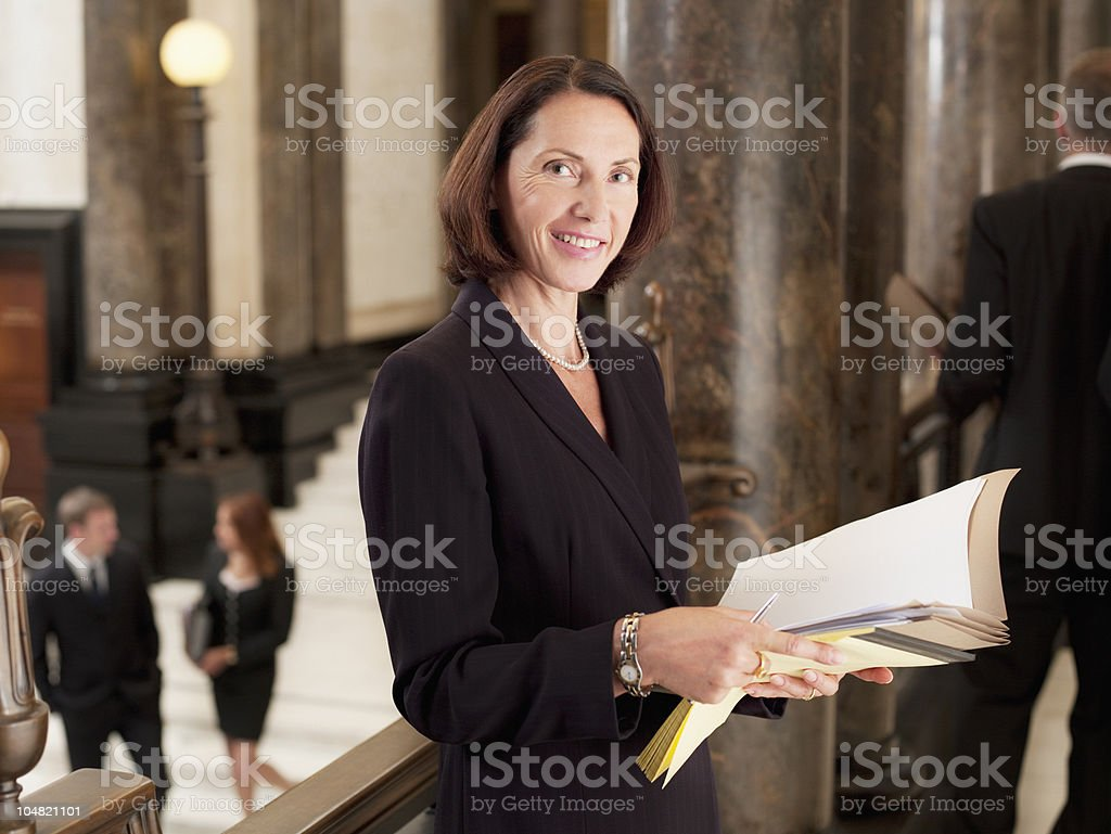 Smiling lawyer reviewing case file in corridor stock photo