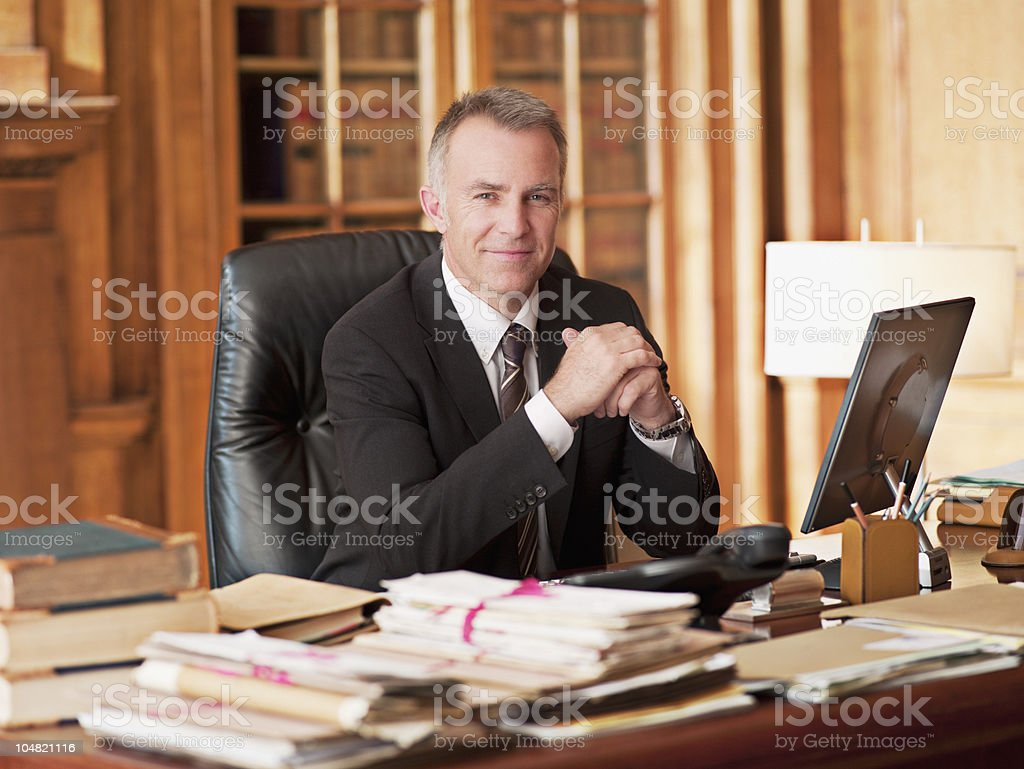 Smiling lawyer sitting at desk in office stock photo