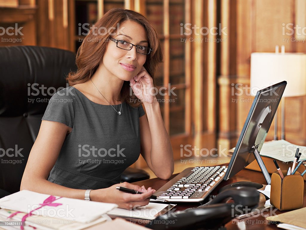 Smiling lawyer sitting at laptop in office stock photo