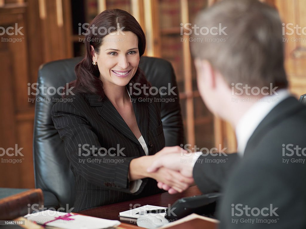 Smiling lawyers shaking hands in office stock photo