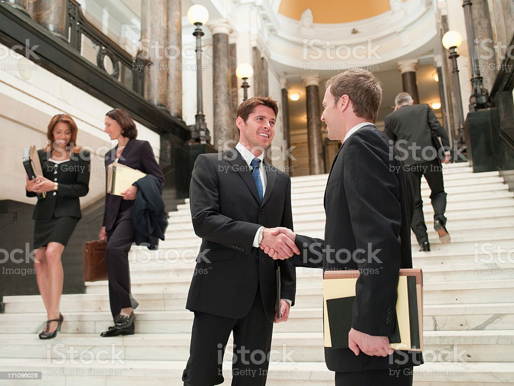 Smiling lawyers shaking hands on stairs stock photo