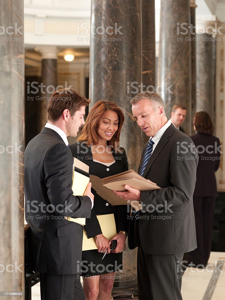 Smiling lawyers talking in corridor stock photo