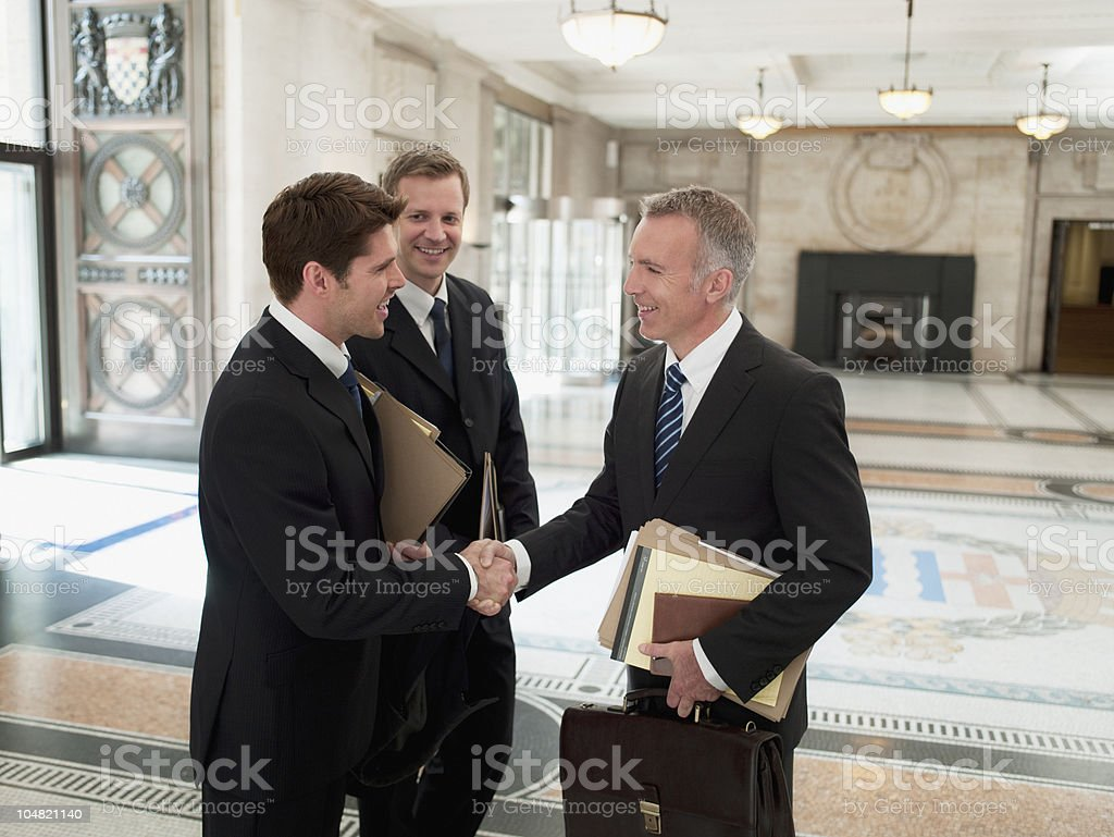 Smiling lawyers with files shaking hands in lobby stock photo