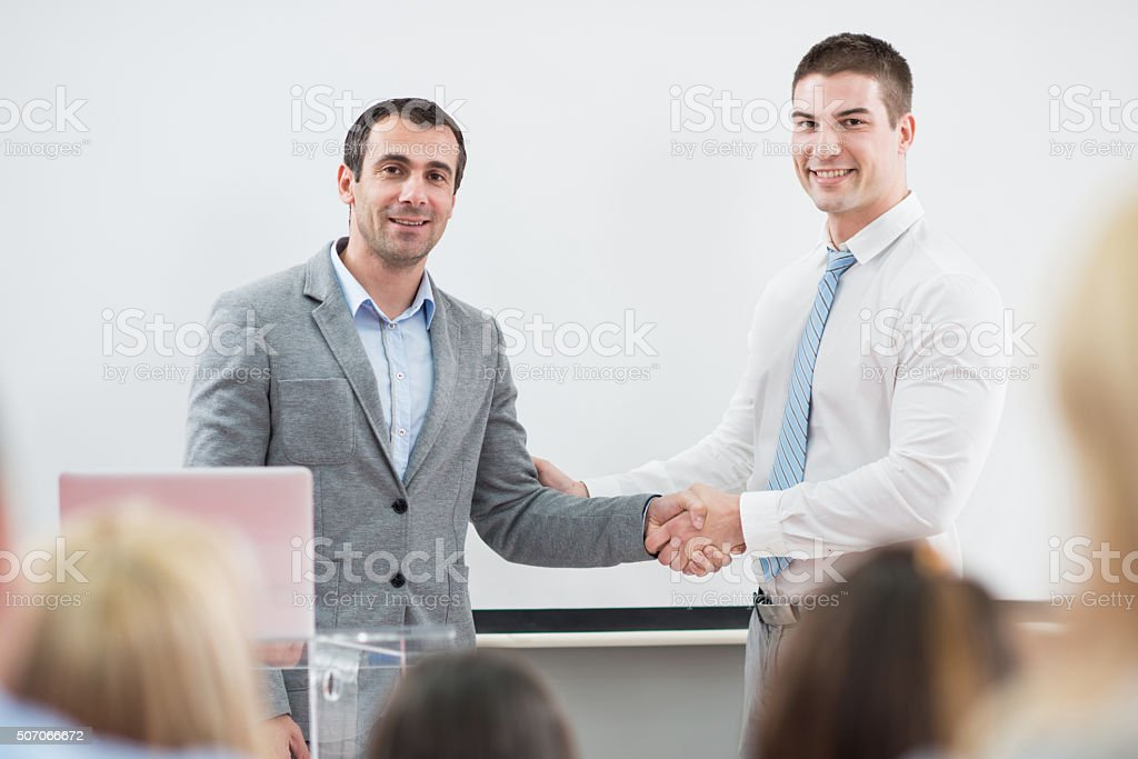 Smiling lecturer and businessman shaking hands in convention center. stock photo