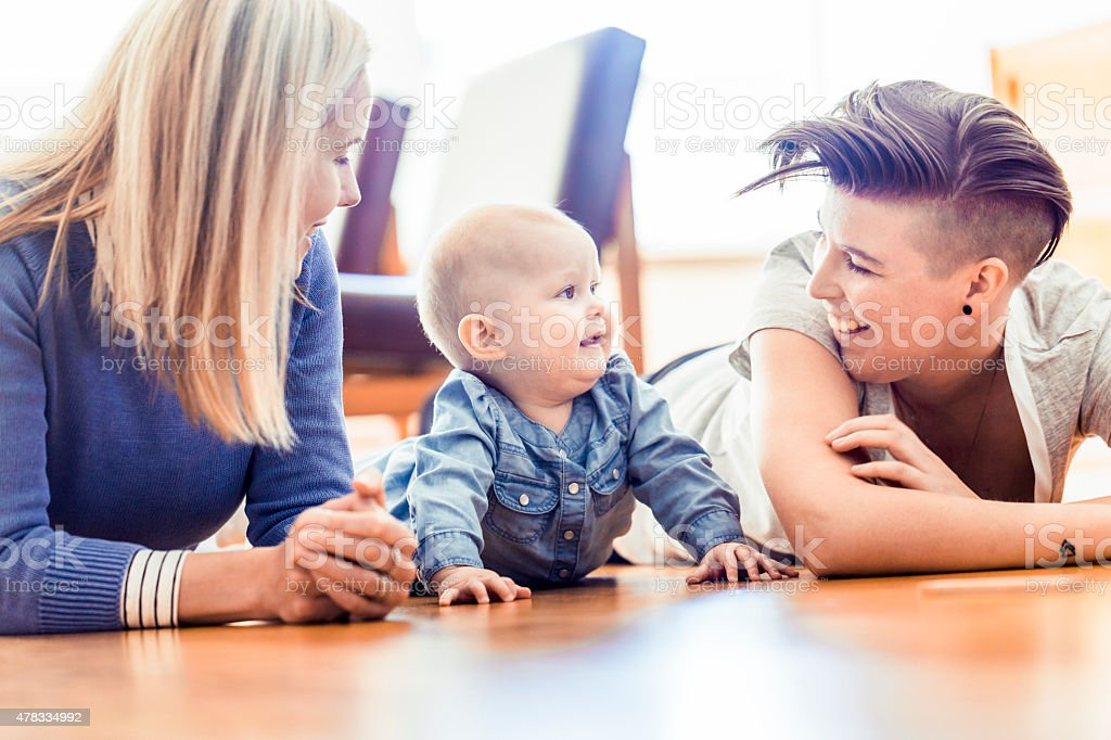 Smiling lesbians with baby lying on hardwood floor stock photo