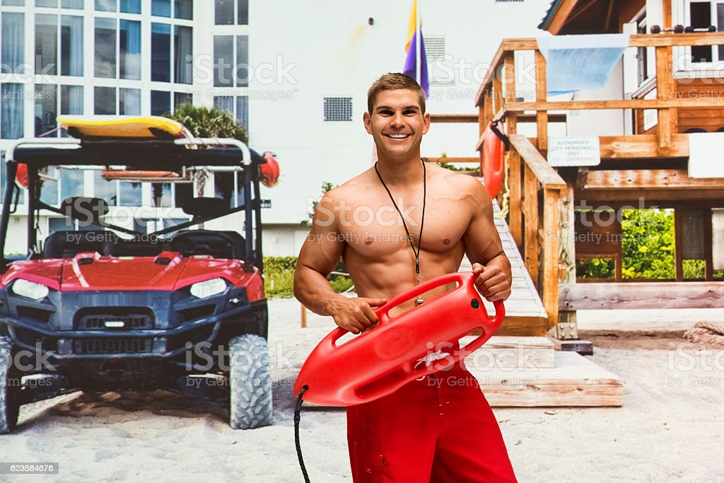 Smiling lifeguard holding life belt at the beach stock photo