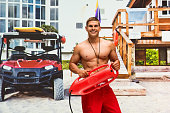 Smiling lifeguard holding life belt at the beach