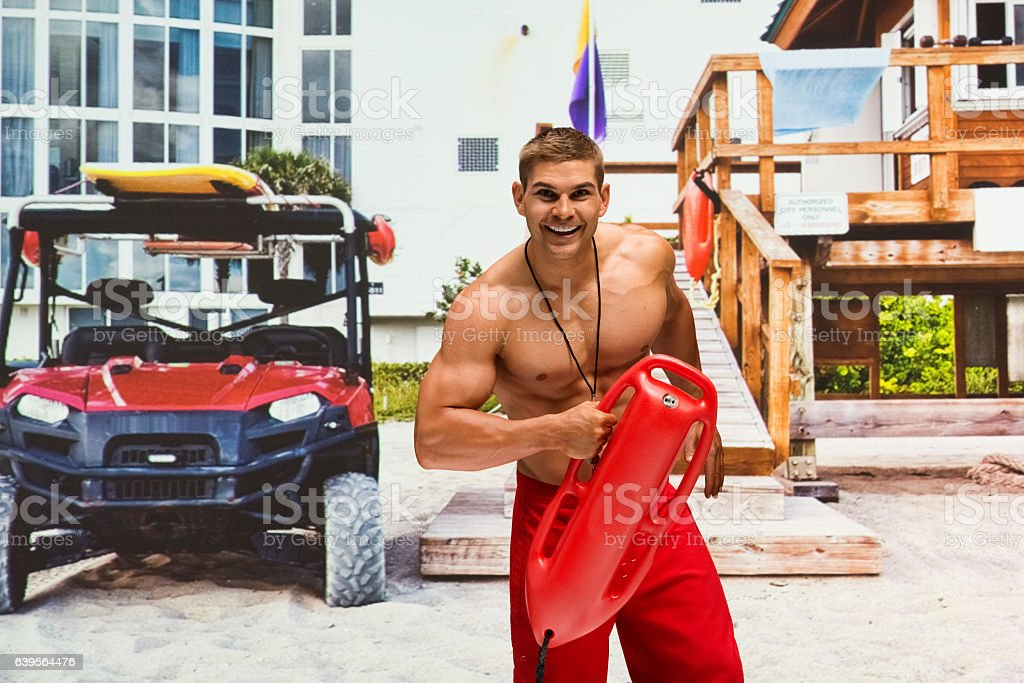 Smiling lifeguard holding life belt outdoors stock photo