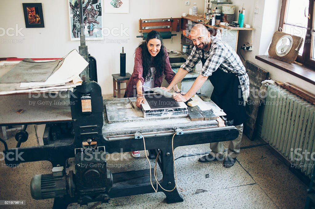 Smiling lithography workers handmaking new pattern at printing house stock photo