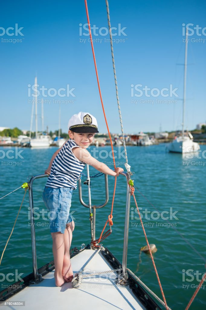 smiling little boy captain aboard luxury boat during the ocean cruise...