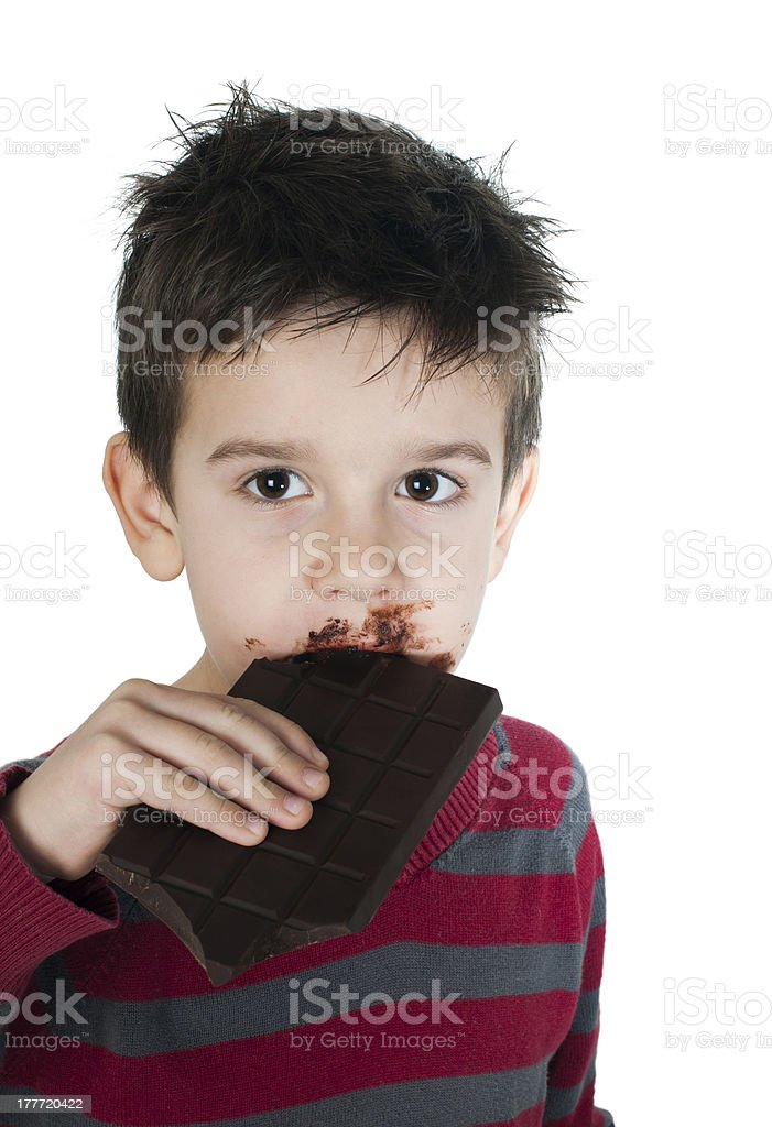 Smiling little boy eating chocolate royalty-free stock photo