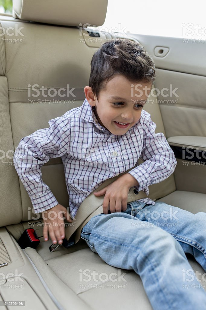 Smiling little boy fastening a seatbelt in the car. stock photo