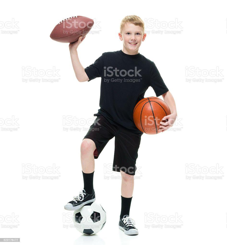 Smiling little boy holding sports balls stock photo