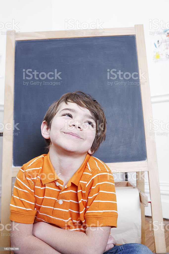 Smiling little boy in front of a blank blackboard royalty-free stock photo