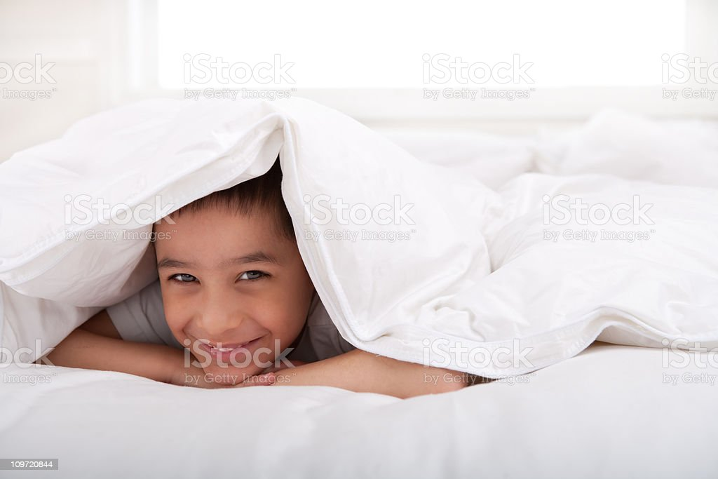 Smiling little boy laying under blanket stock photo